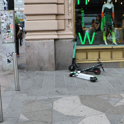 Två stycken elsparkcyklar, av märket Tier och Lime står dåligt parkerade utanför ett skyltfönster. Ena sparkcykeln har fallit över den andra.