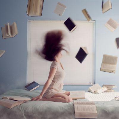 Nuori nainen istuu sängyllä, kirjoja lentelee hänen ympärillään.