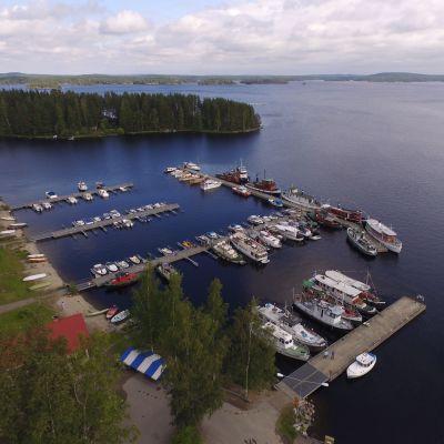 Ilmakuva kesäisestä Heinäveden kirkonkylän satamasta, jossa useita veneitä ja laivoja laiturissa.