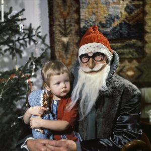 En liten flicka i julgubbens famn på julen. I bakgrunden en julgran.