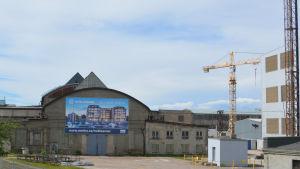 De slitna hamnkvarteren norr om Tallinn centrum håller på att rustas upp, på bilden en skylt av hur det kommer att se ut när det är färdigt, en lyftkran.