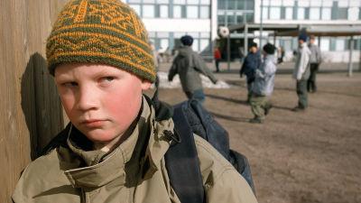 poika katsoo leikkiviä koululaisia koulun pihalla poispäin kääntyneenä.