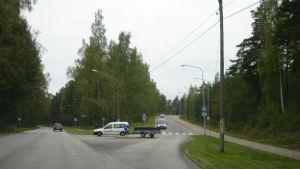Vägkorsning, i mitten en vit bil med en släpvagn.