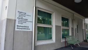 Skylt på en vägg där det står dagkirurgi och Mödrapoliklinik.