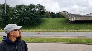 Oliver Orro står framför Maarjamäe minnesmärke och tittar upp mot det.