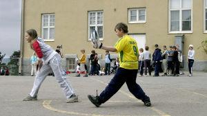 Skolelever som spelar bollspel på skolgård