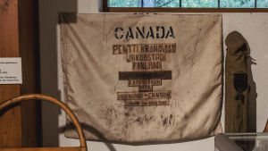 Vanha kelkka, lumikenkiä, ja muita arktiseen liittyvää tavaraa. Seinällä kangas, johon painettu teksti: Canada, Pentti Kronqvist, Jakobstad, Finland.