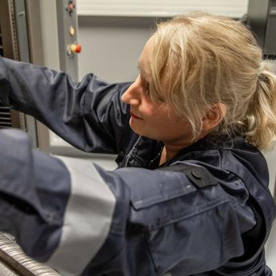 Tekniikan tohtori Anna Keskisaari testaa kuitulujitetun komposiitin vetolujuutta LUT:n laboratoriossa.