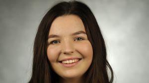 Ung leende kvinna med långt mörkt hår och vit blus.
