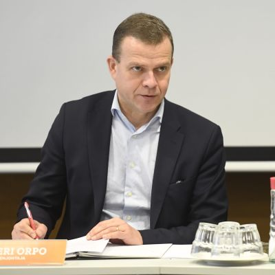 Petteri Orpo sitter vid ett bord.