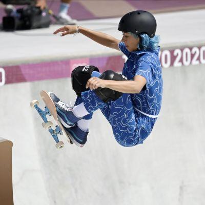 Skateboardare i blå dräkt under sitt åk.
