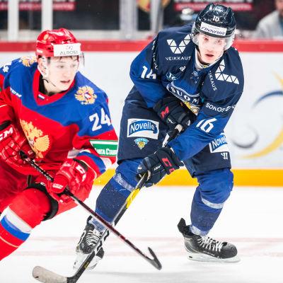 Anton Lundell kämpar om pucken mot en rysk spelare.