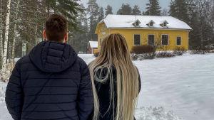 Kaksi anonyymiä henkilöä seisovat Villa Hockeyn edessä selin