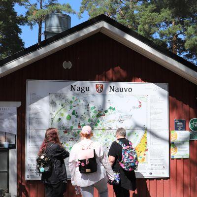 """En skylt med texten """"Nagu"""" och """"Nauvo. Några kvinnor läser skylten."""