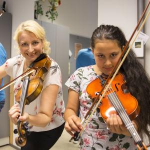Elham ja Bahara opiskelevat viulunsoittoa opettaja Minni Ilmosen johdolla.