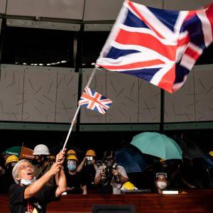En demonstrant viftar med den brittiska flaggan efter att demonstranter stormat lokalstyrets byggnad i Hongkong.