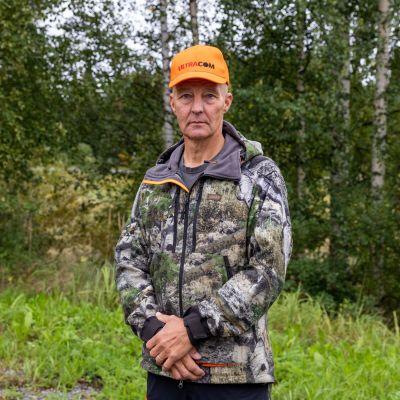 Maastoasuun pukeutunut metsästäjämies katsoo kuvaajaa, taustalla metsämaastoa.