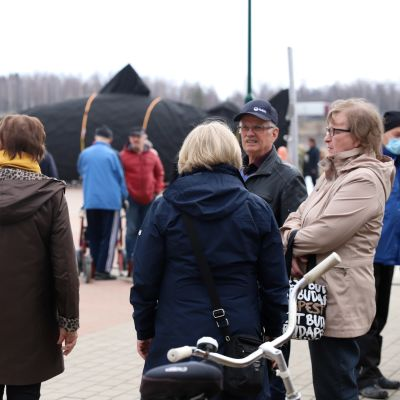 Ihmisiä seisoskelee, taustalla kankailla peitetty Kojamo-veistos Tornionjokirannassa.