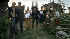Käkriäisen perhe Putkinotkosta. Isännän ja emännän ympärillä on kymmenen lasta sekä mummo. Kesäinen pihamaa, puurakennuksia, yllä rähjäiset vaatteet 1800-luvulta.