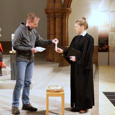 seurakuntapastori auttaa kynttilän sytyttämisessä