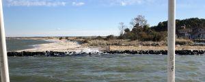 Flörbindelsebåten sveper förbi en strand somo skyddas av en stenmur.