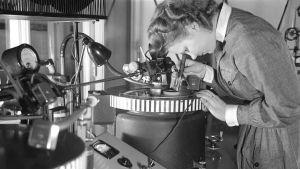 Lotta-pukuinen nainen työssä pikalevyjen äänityslaitteen äärellä 1940-luvulla. Ääniä ja radio-ohjelmia tallennettiin sellakkakalvopintaisille metallilevyille.
