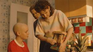 Tre av rollfigurerna från filmen står i köket. Johannes mamma visar en ny docka han ska få.