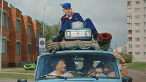 Pojken Johannes sitter på det fullpackade biltaket medan hans familj sitter inne i bilen och kör.