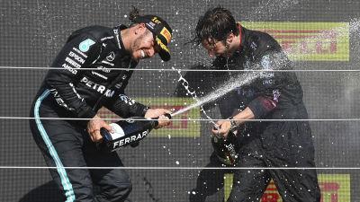 Lewis Hamilton spruzza champagne in passerella.
