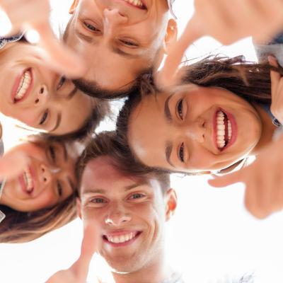 Fem unga tittar ner i kameran och lägger tummen upp.