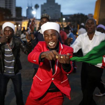 Personer som stöder den sittande presidenten Uhuru Kenyatta jublar och viftar på en flagga i Nairobi medan de väntar att valkommissionen ska bekräfta resultatet i det kenyanska presidentvalet 2017.