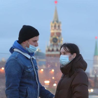 En man och en kvinna med munskydd. Mannen har dragit ner sitt skydd så att näsan inte är täckt. Personerna står framför Vasilijkatedralen som är ett känt landmärke i Moskva.