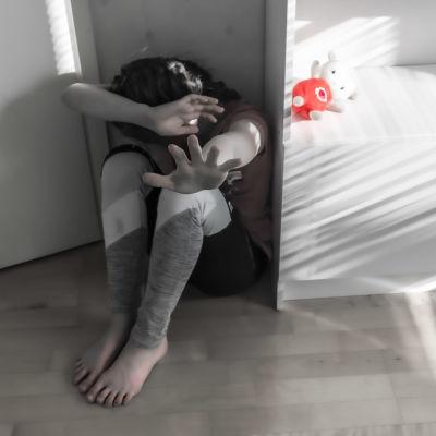Dramatiserad bild, där ett barn sitter i ett hörn och skyddar sitt ansikte och huvud mot ett utomstående hot med sina händer.