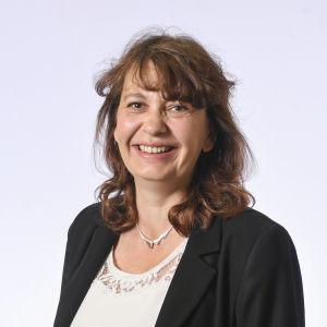 En kvinna med halvlångt mörkt hår i en mörk kavaj och ljus tröja. Hon ler mot kameran.