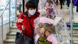Nainen on suojannut itsensä ja lapsensa läpinäkyvällä sadeviitalla Hongkongissa.
