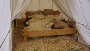 Träsäng fylld med djurfällar. Sängen står i ett tält på underlag av halm.