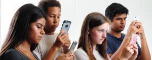 Fyra unga personer försjunkna i sina mobiltelefoner.