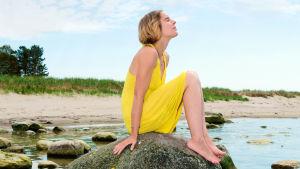 Kvinna sitter på sten i strandbrynet.