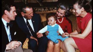 Två män och två kvinnor och en baby sitter i soffa