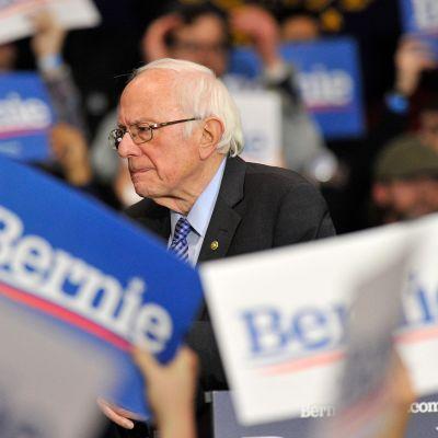 """Bernie Sanders omringad av människor som håller upp plakat med texten """"Bernie""""."""