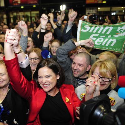 Mary Lou McDonald käsi pystyssä. Taustalla Sinn Feinin nimellä varustettu lakana.