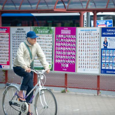 Man med skärmmössa cyklar förbi valplakat i Helsingfors.