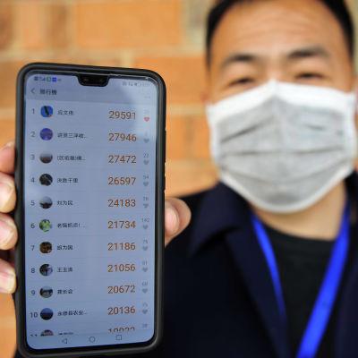 En man håller upp en mobiltelefon och visar hur många steg han har gått varje dag.