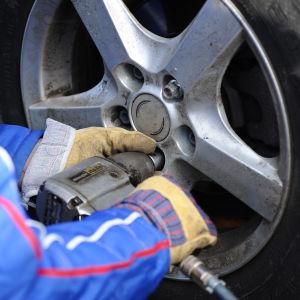 Två händer jobbar med att byta däck med hjälp av en maskin.kbyte