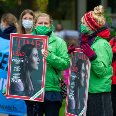 Demonstranter utanför Ständerhuset bär plakat med bild på statsminister Sanna Marin på omslaget till tidskriften Time.
