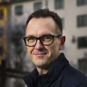 En medelåldersman i svartbågade glasögon ler mot kameran. I bakgrunden syns färgg ranna våningshus.