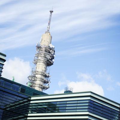 Blåvit himmer och i förgrunden en byggnad bakom vilken Yles tv-torn syns.