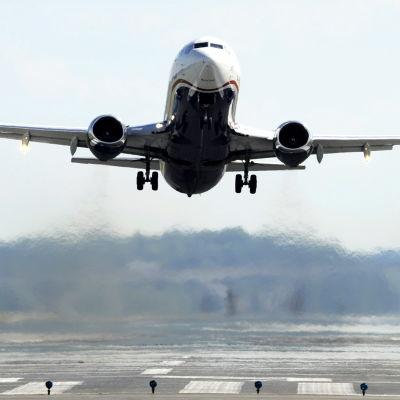 Flygplan som lyfter från flygfält.