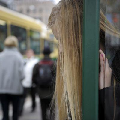 En ung kvinna står och lutar sig mot väggen vid en spårvagnshållplats i Helsingfors.