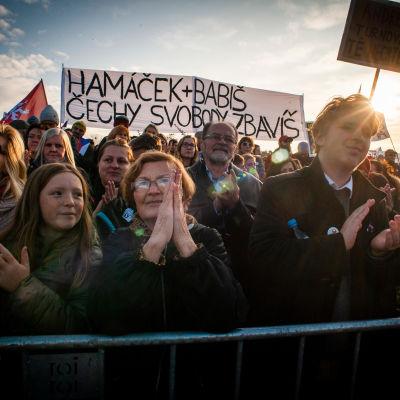 Dmeonstranter står bakom ett lågt stängsel i solnedgången med plakat och tjeckiska flaggor.